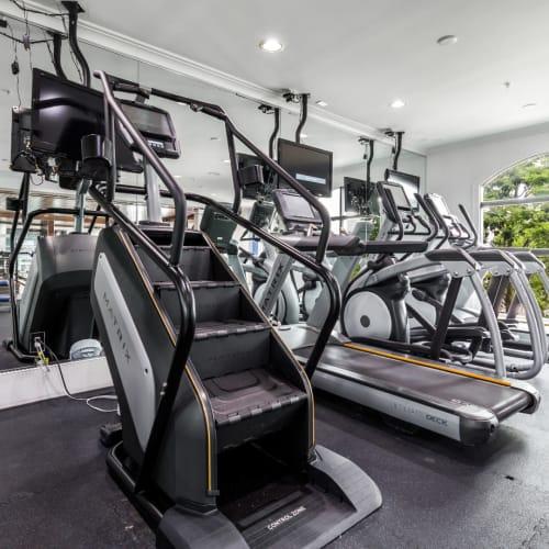 Stair climber, treadmills, and elliptical machines facing mirrors at Marquis Midtown District in Atlanta, Georgia