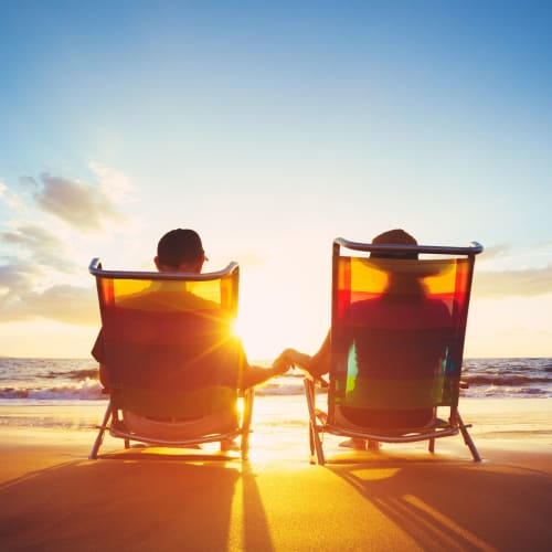 Couple relaxing on beach chairs and enjoying the gorgeous sunset near The Pointe at Siena Ridge in Davenport, Florida
