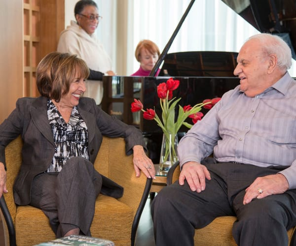 Residents enjoying some lovely piano music at All Seasons Naples in Naples, Florida