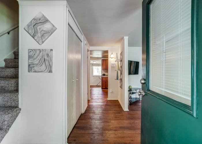 Long view of hallway in resident townhome, showcasing hardwood floors and natural light, at Avalon Townhomes in Hampton, VA
