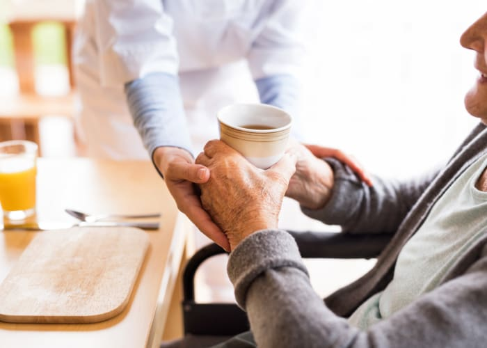 Staff assisting resident with a cup of coffee in the dining room at Westminster Memory Care in Aiken, South Carolina