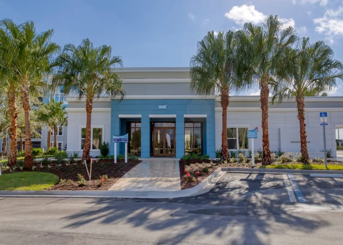 Blue building with palm trees, a property of WRH Realty Services, Inc