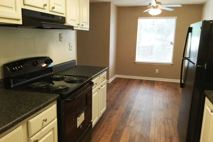 Hardwood floors, sleek black appliances, and more in apartment home kitchen at Abbots Glen