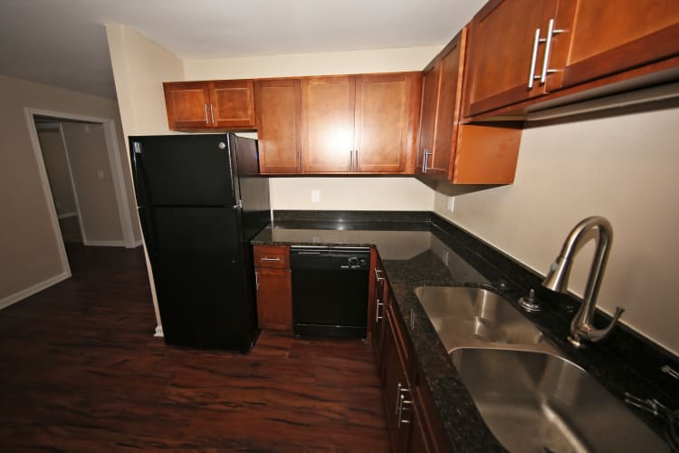 Modern kitchen with sleek black appliances and cherry wood cabinets at The Broadway at East Atlanta