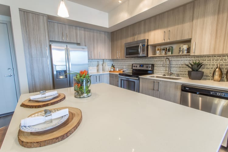 Granite countertops and antique-style cabinetry in a model home's kitchen at Loftin Place Apartments in West Palm Beach, Florida