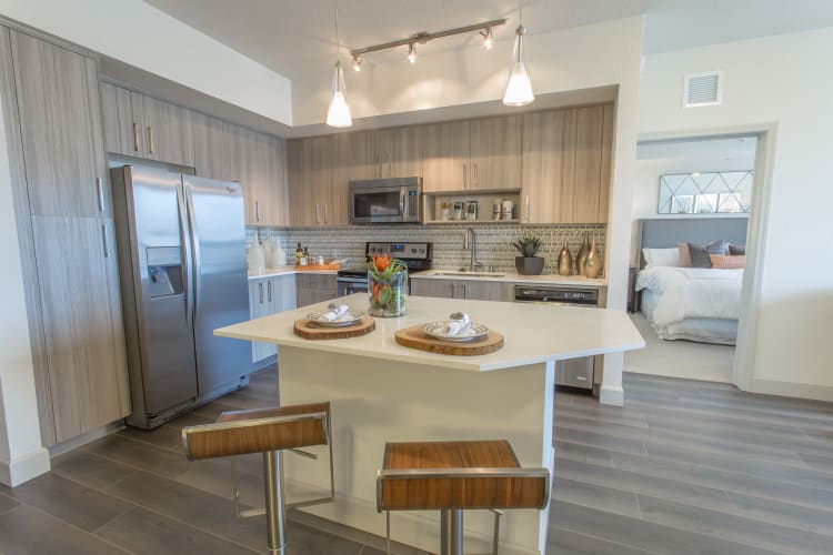 Kitchen with an island in a model home at Loftin Place Apartments in West Palm Beach, Florida