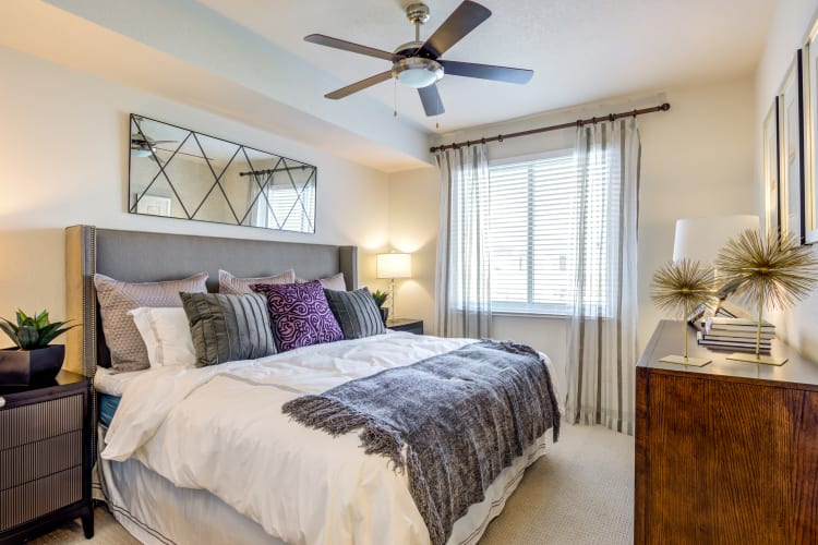 Ceiling fan and plush carpeting in a model home's master bedroom at Loftin Place Apartments in West Palm Beach, Florida