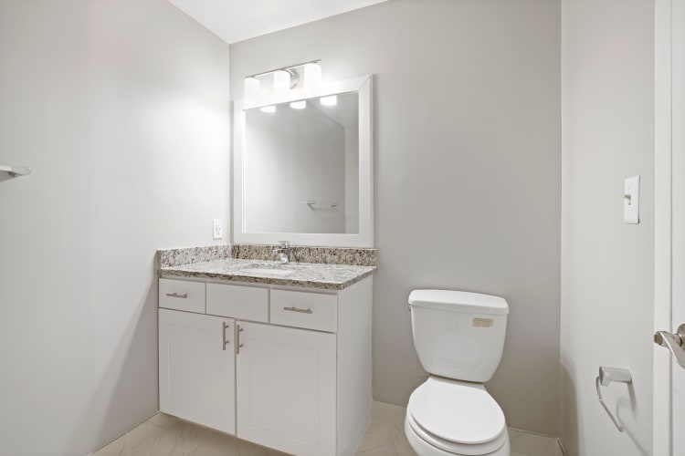 Bathroom with white cabinets and a vanity mirror at 222 Saratoga in Baltimore, Maryland