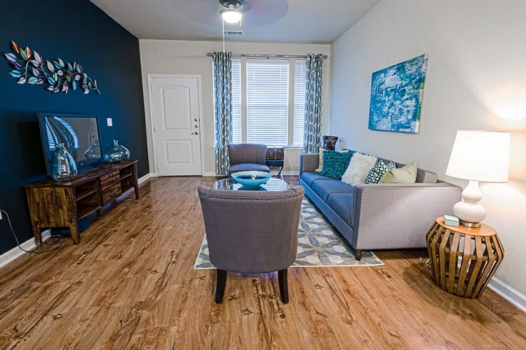 Spacious living room with wood-style floors at Sage Corpus Christi in Corpus Christi, Texas