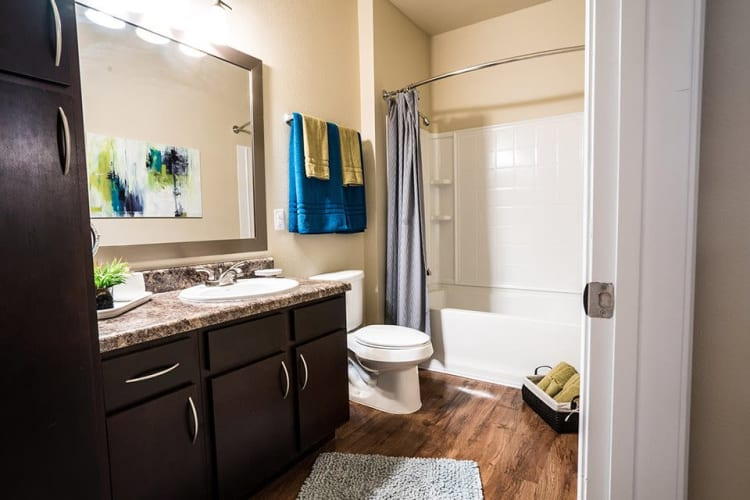 Bathroom with a large vanity mirror at Sage Corpus Christi in Corpus Christi, Texas