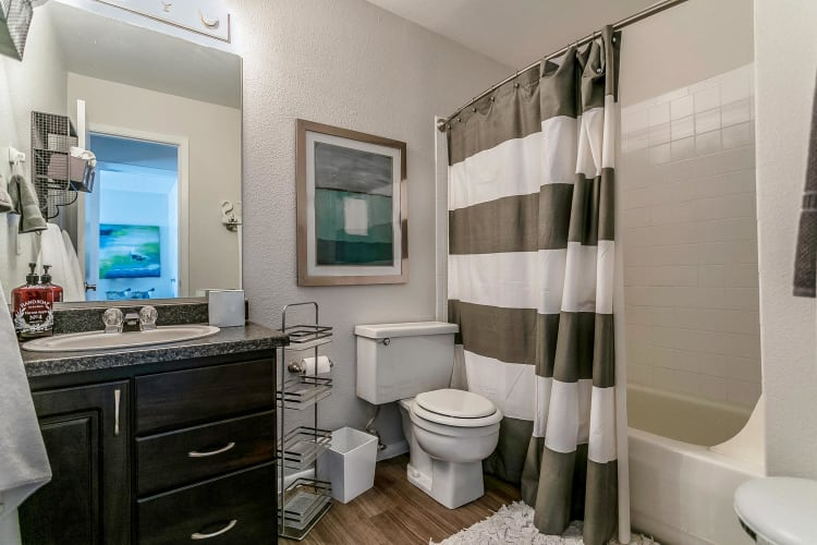 Bathroom with granite countertop and a large vanity mirror in a model townhome at Stratus Townhomes in Westminster, Colorado