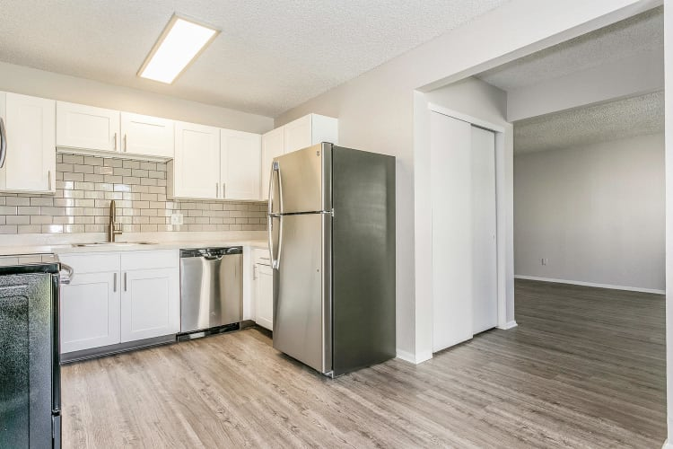 Modern kitchen with stainless-steel appliances and a subway tile backsplash in a model townhome at Stratus Townhomes in Westminster, Colorado
