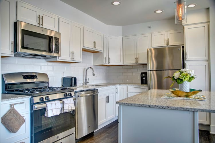 Modern kitchen with granite countertops and stainless-steel appliances in a model home at Watergate Pointe in Annapolis, Maryland