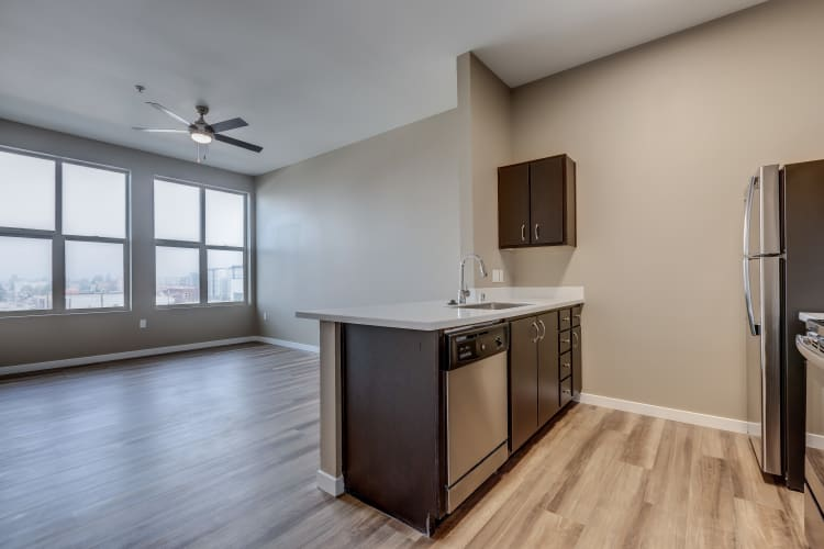 Open-floor layout with a ceiling fan in living room at Lumen Apartments in Everett, Washington