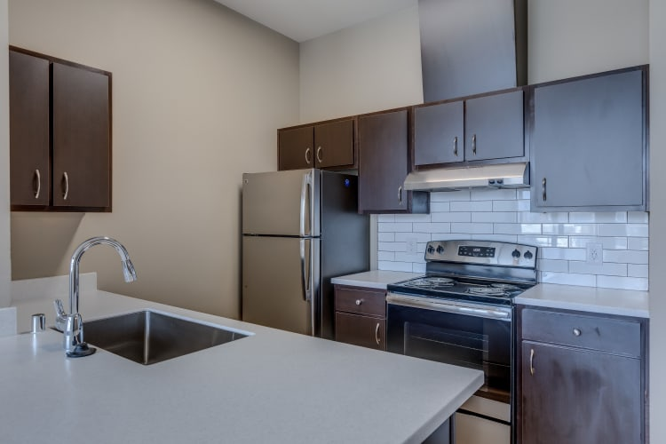 Kitchen with stainless-steel appliances and a tiled back splash at Lumen Apartments in Everett, Washington