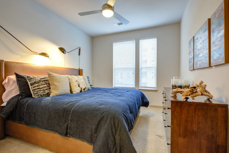 Master bedroom with plush carpeting and a ceiling fan in a model home at Regatta Sloan's Lake in Denver, Colorado