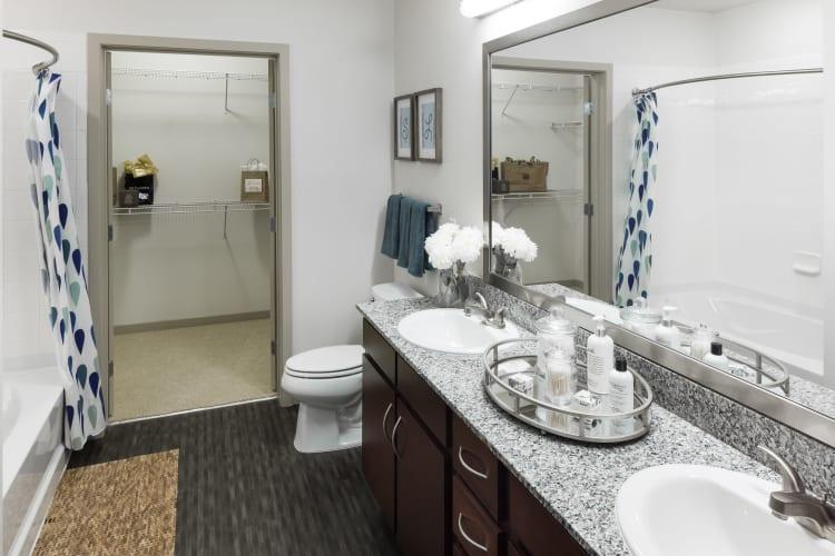 Luxurious en suite bathroom with dual sinks, a granite countertop, and oversized vanity mirror in a model home at Regatta Sloan's Lake in Denver, Colorado