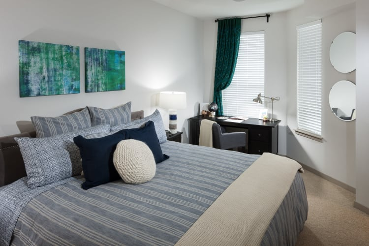 Guest bedroom with large windows in a model home at Regatta Sloan's Lake in Denver, Colorado