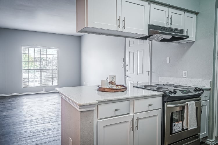 Modern kitchen with white cabinetry and stainless-steel appliances in an apartment home at Azure Apartments in Corpus Christi, Texas