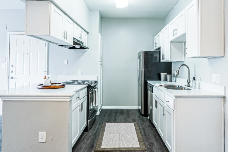 Recently renovated kitchen with granite countertops in an apartment home at Azure Apartments in Corpus Christi, Texas