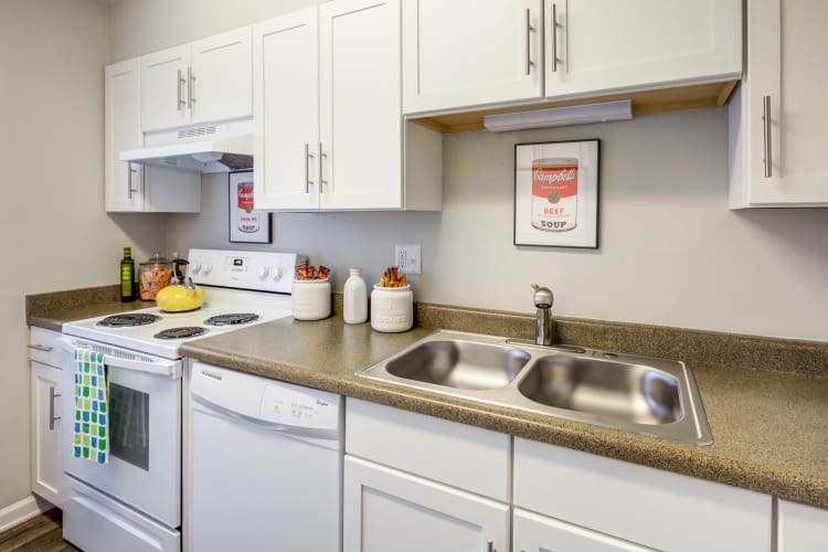 Modern kitchen with granite countertops and white appliances in a model home at The Ranch at Bear Creek Apartments & Townhomes in Lakewood, Colorado