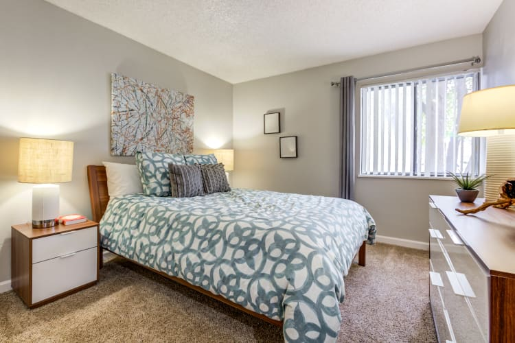 Well-furnished master bedroom in a model home at The Ranch at Bear Creek Apartments & Townhomes in Lakewood, Colorado