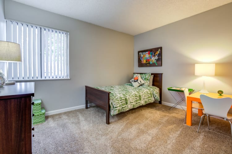 Children's bedroom with plush carpeting and plenty of room to play in a model home at The Ranch at Bear Creek Apartments & Townhomes in Lakewood, Colorado