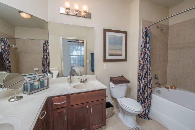 Bathroom with tiling and a large vanity mirror at Villas Tech Ridge in Pflugerville, Texas