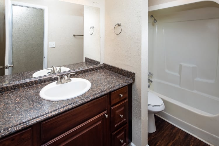 Bathroom with large vanity mirror and wooden cabinets in an apartment home at Premier Apartments in Austell, Georgia