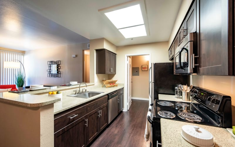 An updated kitchen with brown cabinetry at Sierra Del Oro Apartments in Corona, California