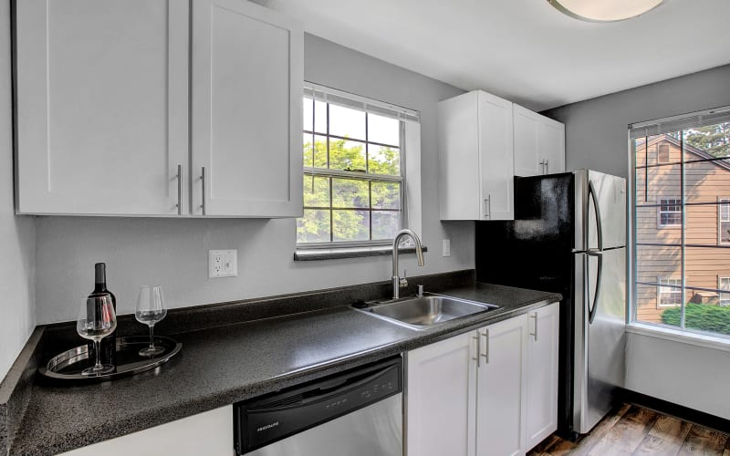 Renovated kitchen with white cabinets and stainless steel appliances at Waters Edge Apartments in Kent, Washington