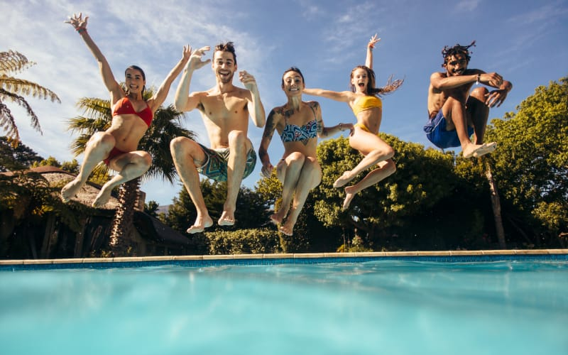 Friends jumping into the swimming pool at Sundance Apartments in College Station, Texas