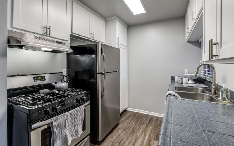 A renovated kitchen with white cabinets at Kendallwood Apartments in Whittier, California