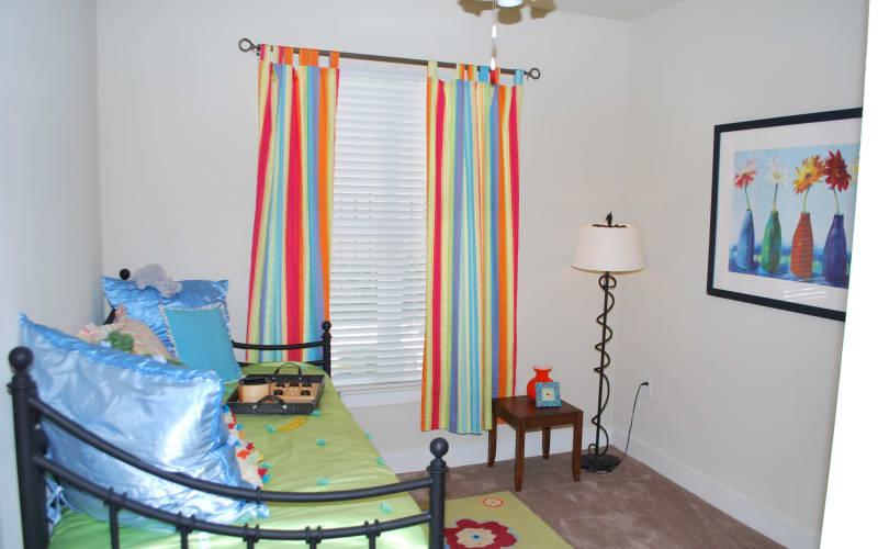 A colorfully decorated apartment bedroom at Providence Mockingbird Towers in Dallas, Texas