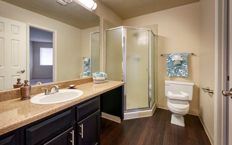 Renovated bathroom with brown cabinets at Bluesky Landing Apartments in Lakewood, Colorado
