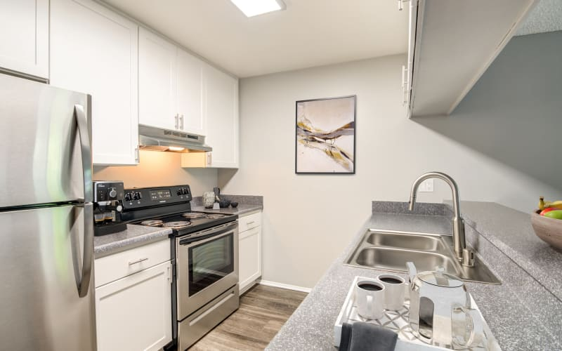Renovated kitchen with white cabinets and stainless steel appliances at Hillside Terrace Apartments in Lemon Grove, California