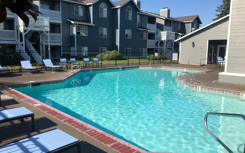 The sparkling resort-style swimming pool with new lounge chairs at Walnut Grove Landing Apartments in Vancouver, Washington