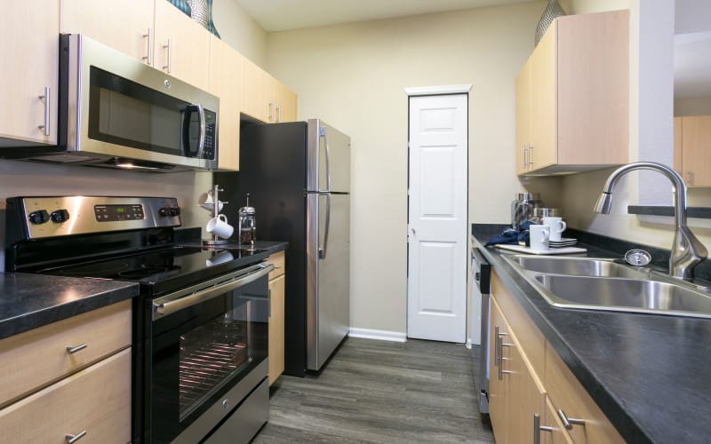 Renovated kitchen with stainless steel appliances at Crestone Apartments in Aurora, Colorado