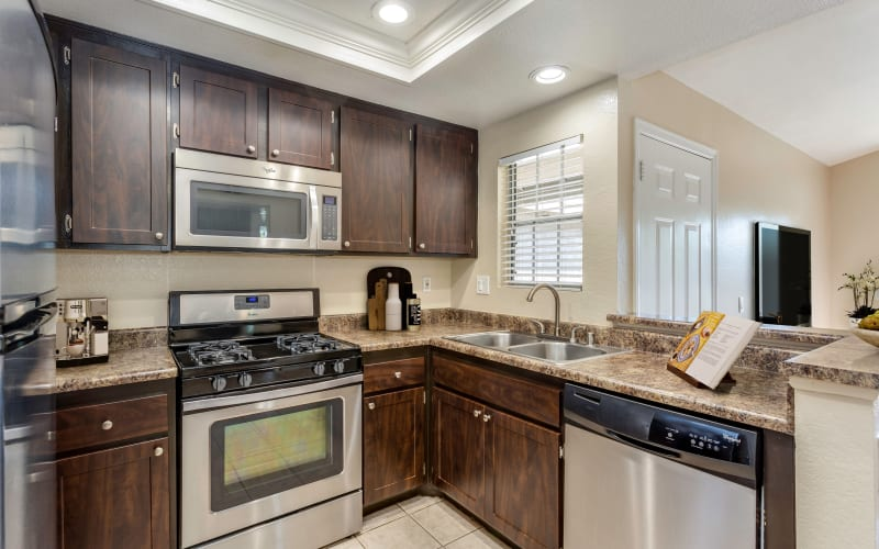 Espresso cabinets, stainless steel appliances, and ceramic tile floors in the kitchen at Village Oaks in Chino Hills, California
