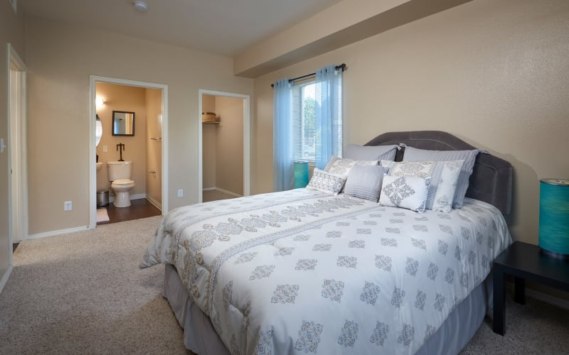 Spacious master bedroom with attached bathroom at Crossroads at City Center Apartments in Aurora, Colorado