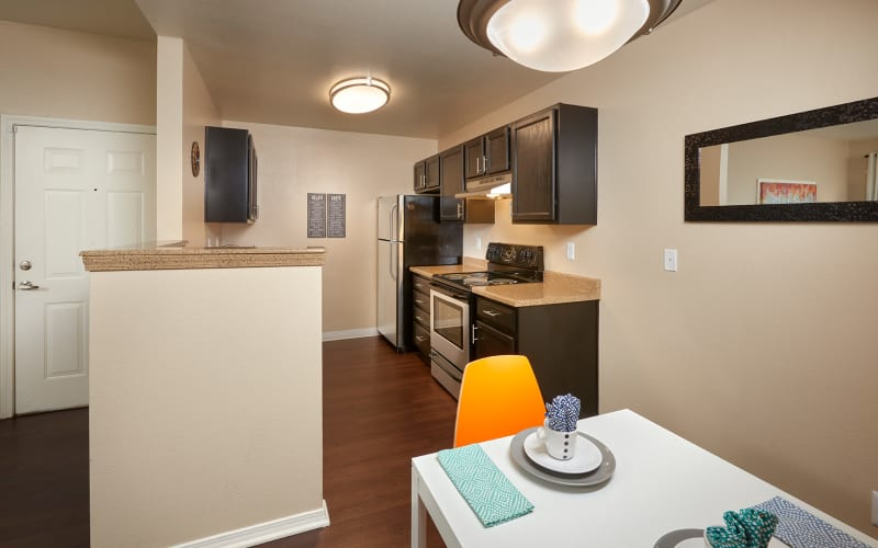 Renovated kitchen with espresso cabinets at Crossroads at City Center Apartments in Aurora, Colorado
