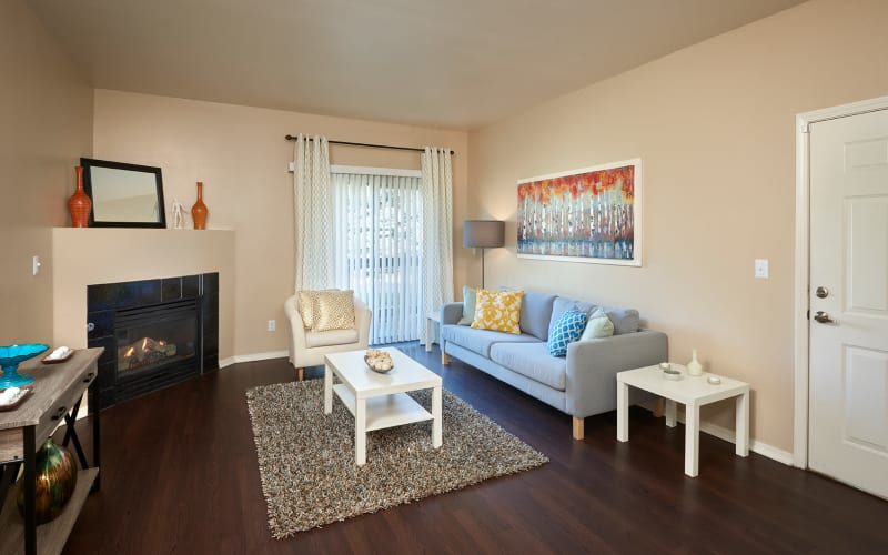 Living room with a gas fireplace at Crossroads at City Center Apartments in Aurora, Colorado