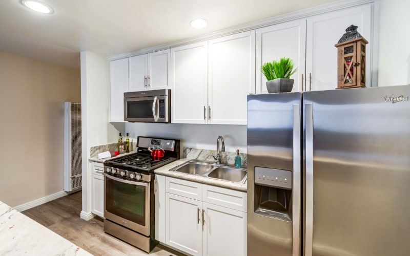 Kitchen with an island and stainless steel appliances in a model home at Mediterranean Village in West Hollywood, California
