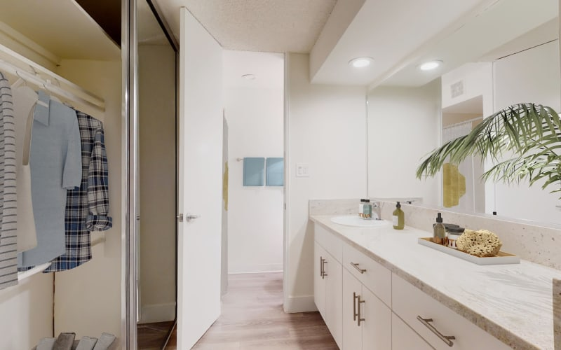 Extra closet space and a large vanity mirror in a studio apartment's bathroom at Mediterranean Village in West Hollywood, California