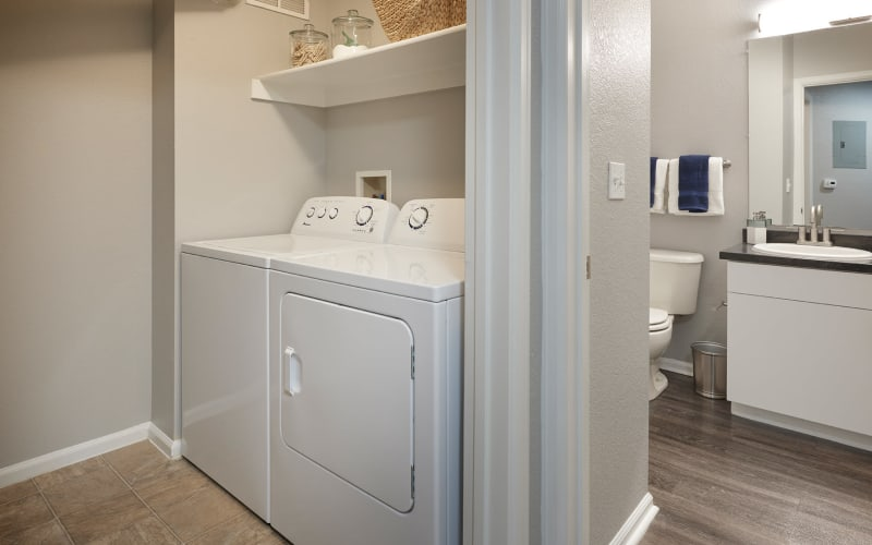 Side by side washer dryer and bathroom at Crestone Apartments in Aurora, Colorado