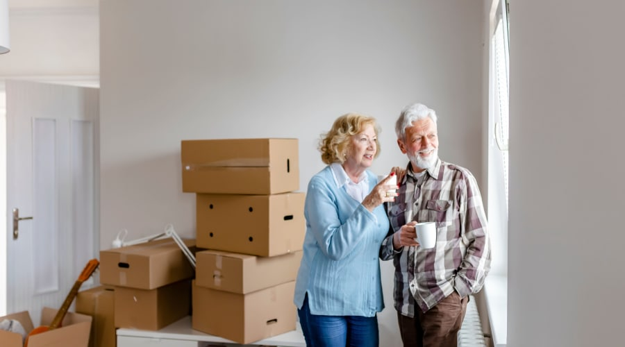 An older couple in their new house with unpacked boxes near KO Storage of Juneau in Juneau, Wisconsin