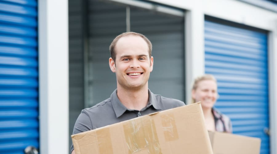 A man and woman carrying boxes out of a unit at KO Storage of Minot in Minot, North Dakota