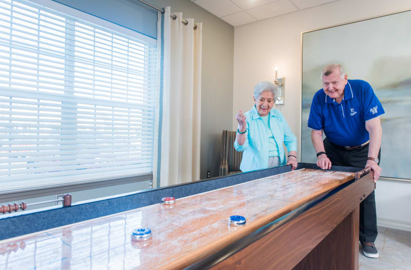 Residents playing shuffleboard at The Welstone At Mission Crossing in Mission, KS