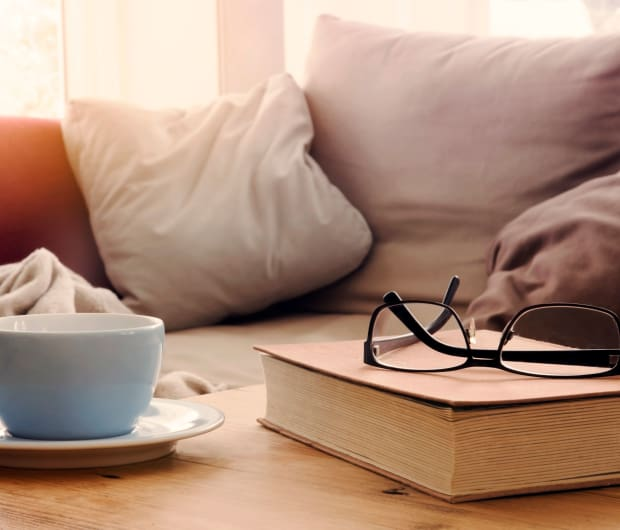 Books and reading glasses on coffee table at Charlesgate Apartments in Towson, Maryland