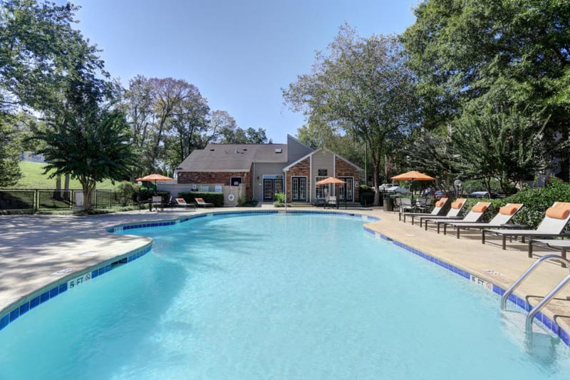 Resort-style swimming pool surrounded by chaise lounge chairs and mature trees at Allegro on Bell in Antioch, Tennessee